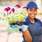 Female garden store worker holding up flowers