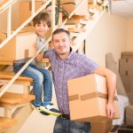 Father and child holding moving boxes